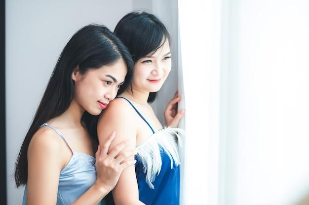 두 명의 아름다운 태국 여성 그들은 잠옷을 입고 창가에 서서 껴안고 포옹했습니다.