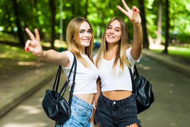Two beautiful tourist women with peace gesture while walking with bags in park