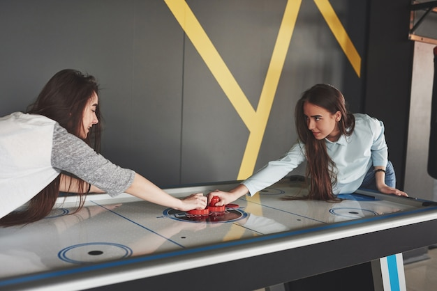 Две красивые девочки-близнецы играют в воздушный хоккей в игровой комнате и развлекаются.