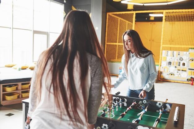 Две красивые девочки-близнецы играют в настольный футбол и веселятся.