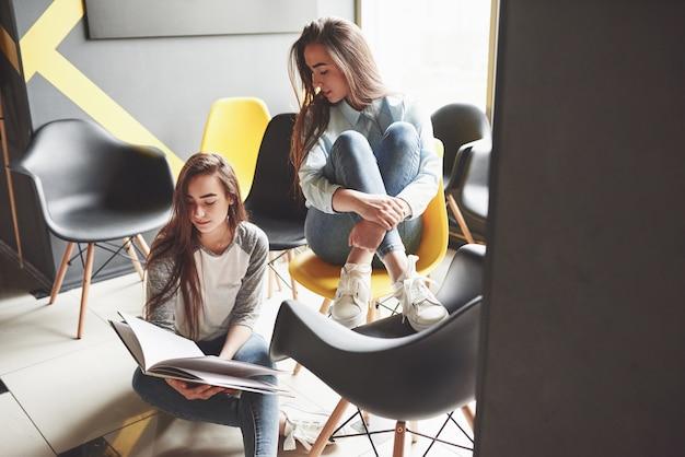 Утром две красивые близняшки проводят время за чтением книги в библиотеке. сестры отдыхают в кафе и веселятся вместе