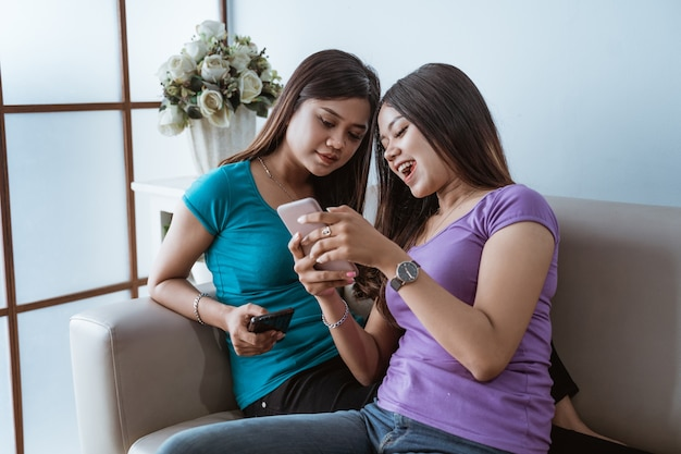 Two beautiful twin sister women looking at the mobile phone at home