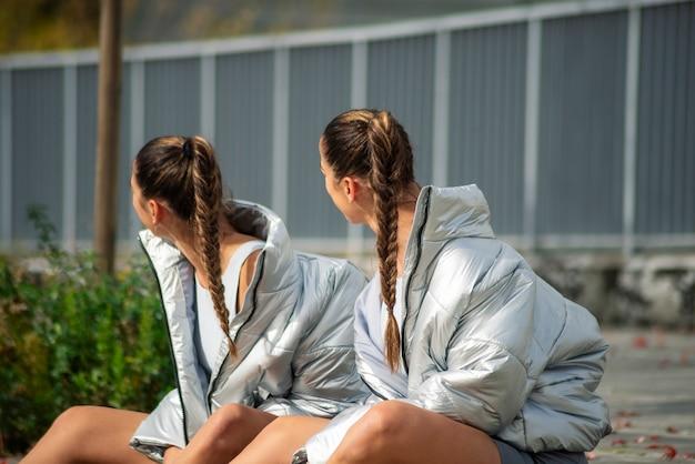 灰色のジャケットを着た2人の美しい双子の姉妹