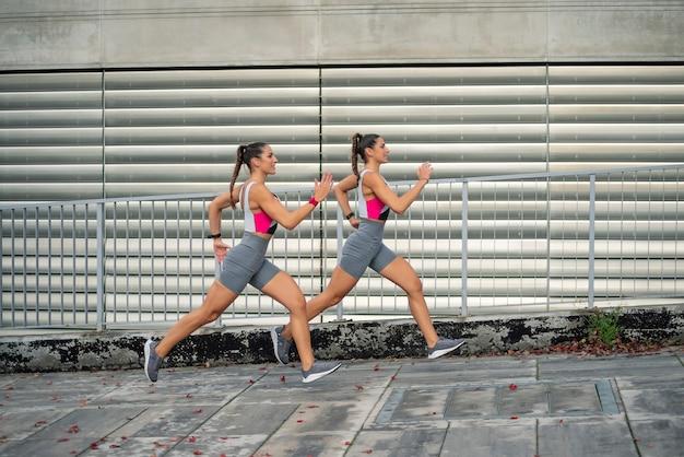 スポーツウェアで街を走り回る2人の美しい双子の姉妹