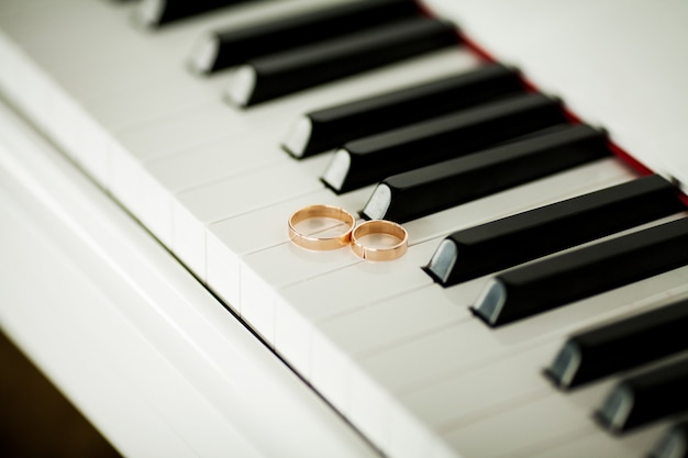 Two beautiful wedding rings on piano keyboard in close-up