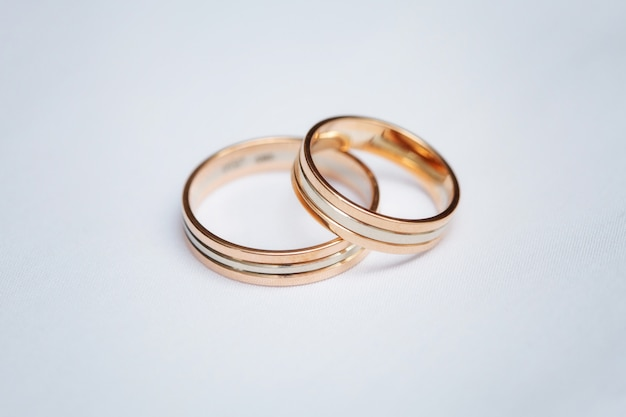 Two beautiful wedding rings on white surface, close up