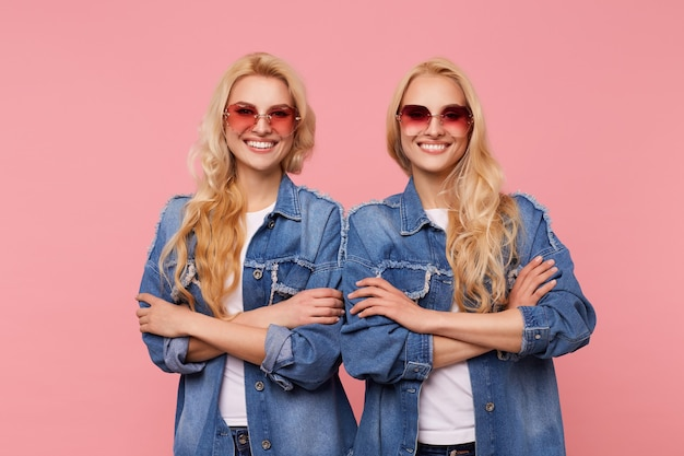 Two beautiful white-headed females in sunglasses and jeans coats folding their hands on chest while standing over pink background, smiling widely while looking cheerfully at camera