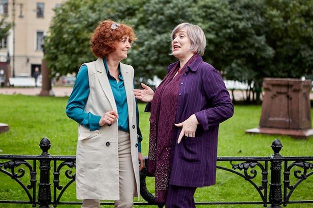 두 명의 아름다운 백인 중년 여성이 러시아 상트 페테르부르크의 중심에 서있는 동안 이야기하고 있습니다.