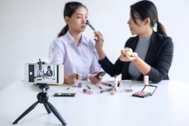Бизнес в интернете в социальных сетях. two beautiful woman blogger демонстрирует настоящее учебное пособие по косметике и транслирует потоковое видео в прямом эфире в социальную сеть во время записи онлайн-обучения.