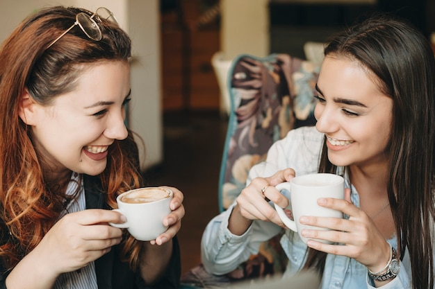 Two beautiful woman drinking coffee and laughing while storytelling while sitting in a cafe.