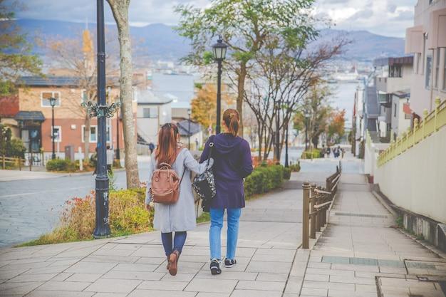 일본 홋카이도 하치만 자카 슬로프에서 거리를 걷는 두 아름다운 여자