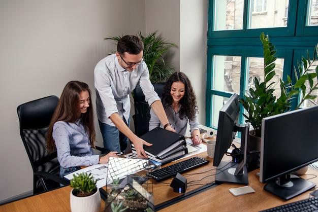 세련 된 셔츠에 남자 문서 폴더를 가져 오는 동안 현대 사무실에서 건축가 프로젝트에서 작업하는 두 아름 다운 여자.
