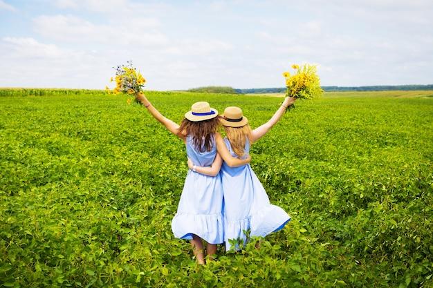 Две красивые подруги в шляпах обнимаются в зеленом поле