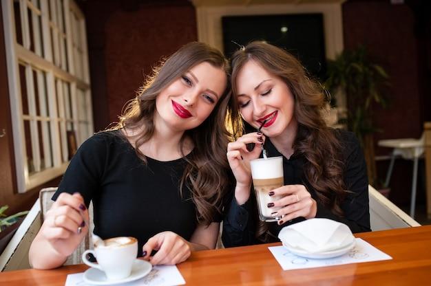 Две красивые женщины пьют кофе