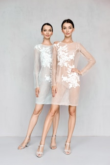 Two beautiful womans wearing pale transparent dresses with lace detailing posing in an identical manner
