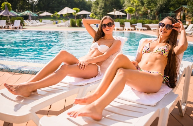 Two beautiful women are lying on chaise-longue poolside.