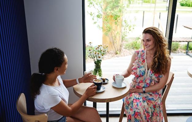 会議で2人の美しい女性が、居心地の良いカフェテリアでコーヒーを飲みながら、カジュアルな雰囲気の中でビジネスの問題について話し合います。コーヒー休憩時間