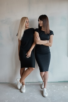 Two beautiful women in black dresses