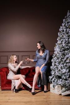 ファッションドレスと一緒にクリスマスを祝う2人の美しい女性。家でのクリスマス