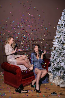 패션 드레스와 함께 크리스마스를 축 하하는 두 아름 다운 여자. 집에서 크리스마스