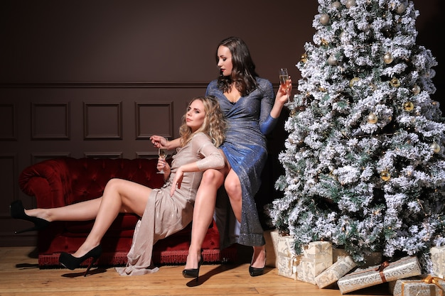 Two beautiful women celebrating christmas together with fashion dress. christmas at home