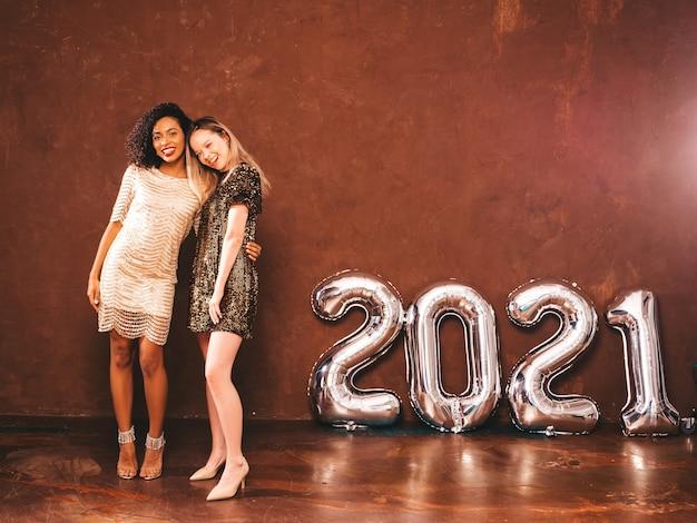 세련 된 새해를 축하하는 두 명의 아름다운 여성. 해피 화려한 여성