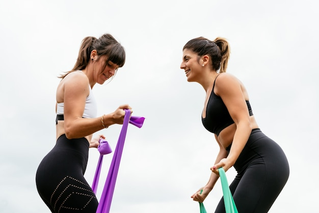 Two beautiful women doing fitness with a rubber band on a white background