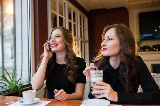 Две красивые женщины пьют кофе и разговаривают по телефону
