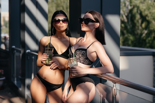 Две красивые женщины наслаждаются летними каникулами с коктейлями у бассейна