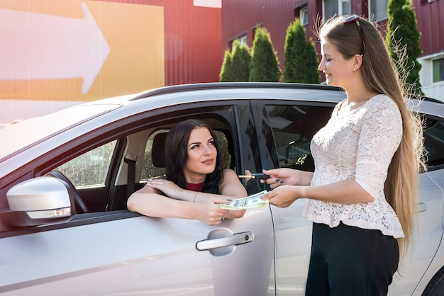 Two beautiful women exchanging by dollars and car keys