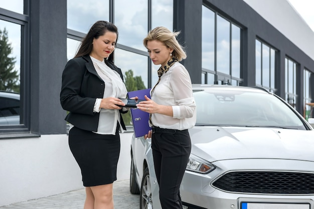 Two beautiful women handshaking near new car standing outside and smilling