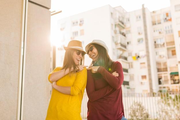 Две красивые женщины веселятся на открытом воздухе на закате. городской фон. стиль жизни
