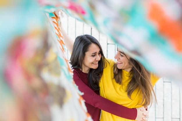 Две красивые женщины веселятся на открытом воздухе на закате с платком. городской фон. стиль жизни