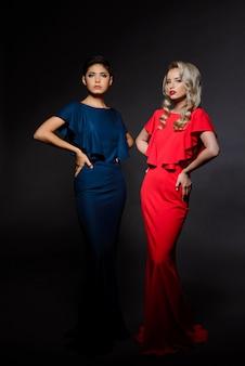 Две красивые женщины в вечерних платьях позируют