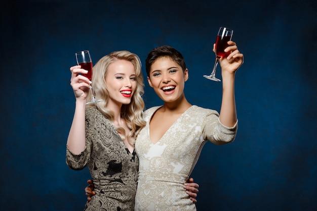 Две красивые женщины в вечерних платьях улыбаются, держа бокалы