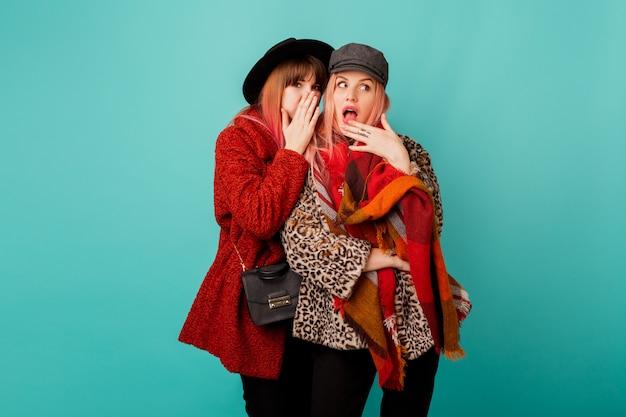 スタイリッシュなフェイクファーコートとターコイズブルーの壁でポーズウールスカーフで2人の美しい女性