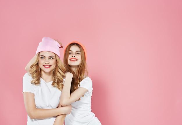 白いtシャツの友情の2人の美しい女性がピンクの背景を抱擁