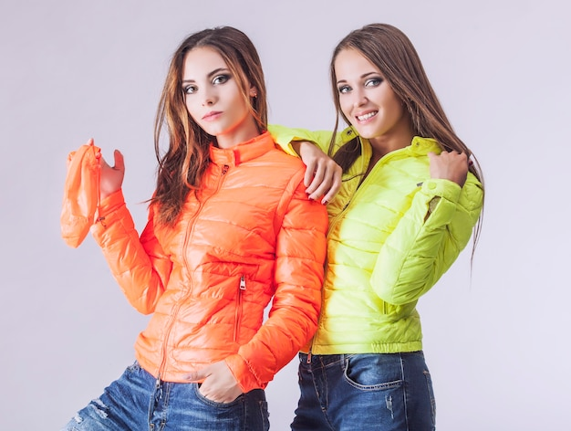 겨울 밝은 재킷에 두 명의 아름다운 여성. 밝은 표면에 세련된 옷을 입은 모델