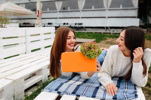 Две красивые женщины лежат на скамейке и дарят друг другу подарки