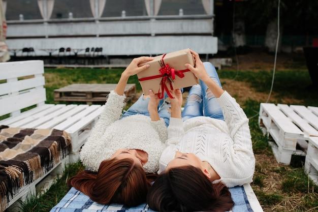 Две красивые женщины лежат на скамейке и распаковывают подарок