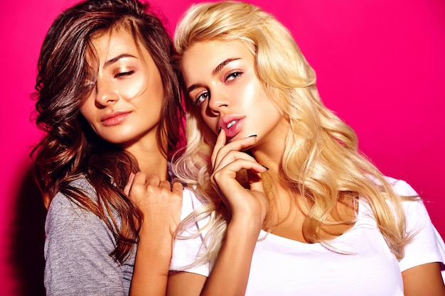Two beautiful women models  with  makeup and clean healthy skin face on pink wall