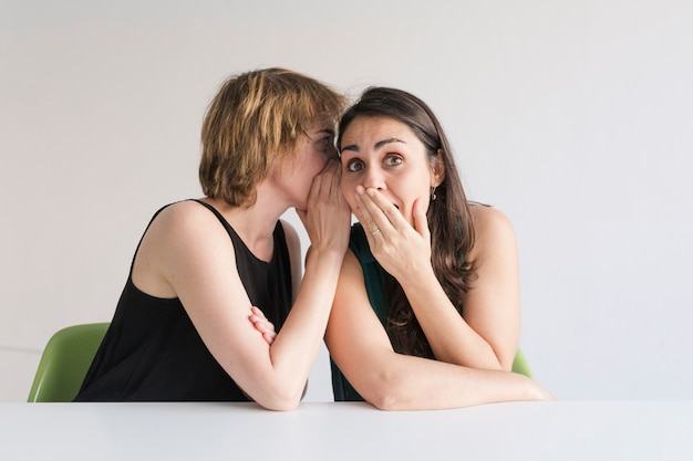 白い背景の上の2人の美しい女性。ブロンドの女の子は耳で秘密を彼女のブルネットの友人に伝えていて、彼女は驚いているようです。友情と秘密の概念