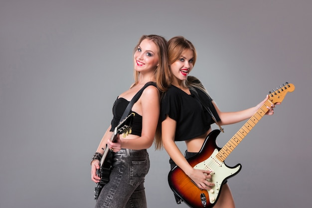 Two beautiful women playing guitars