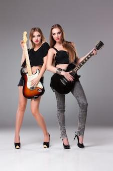 Две красивые женщины играют на гитарах