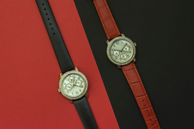 Two beautiful women's watches are on black and red backgrounds. watch with crystals