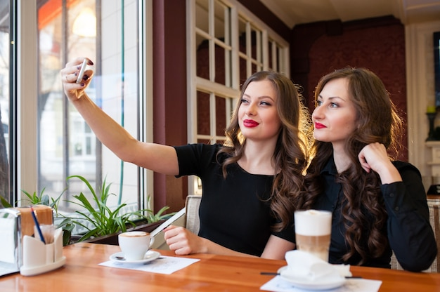 Two beautiful women do selfie and drink coffee