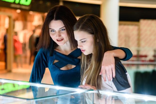 Две красивые женщины делают покупки в торговом центре