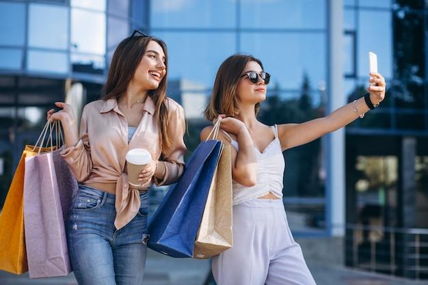 Две красивые женщины делают покупки в городе
