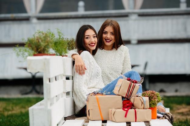 Due belle donne sedute su una panchina, tenendo in mano i regali e guardando