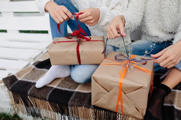 Due belle donne sedute su una panchina e tenendo in mano i regali, vista ravvicinata